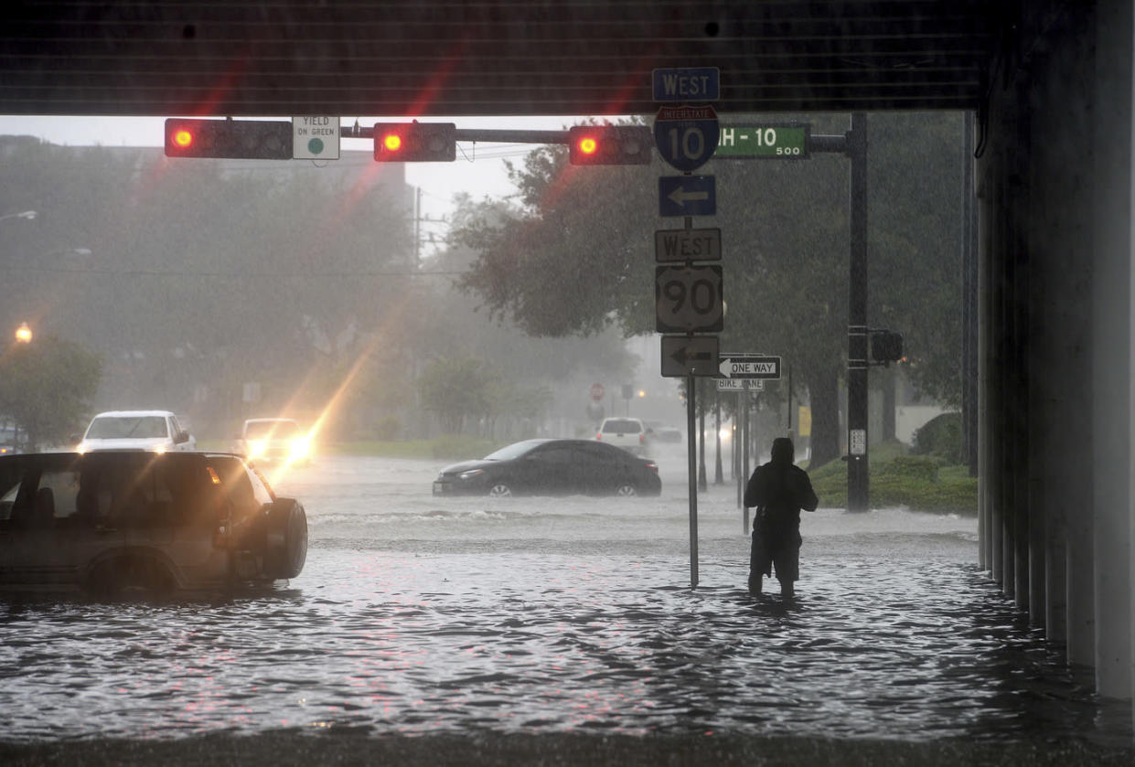 A man makes his way under the I-10 overpass where several roads remained heavily flooded throughout the afternoon, Sept. 19, 2019 in Beaumont, Texas. (Photo: Kim Brent/The Beaumont Enterprise via AP)