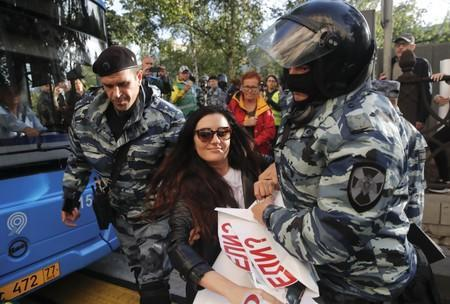 Law enforcement officers detain a woman after a rally to demand authorities allow opposition candidates to run in a local election in Moscow