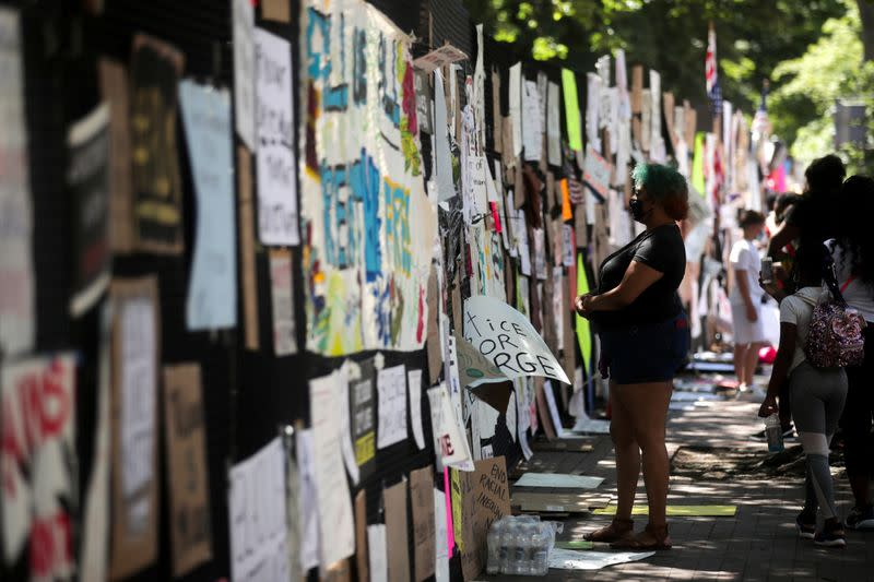 FILE PHOTO: People gather to view protest signs now affixed to the fence around Lafayette Square at the scene where protesters clashed with police near the White House in Washington