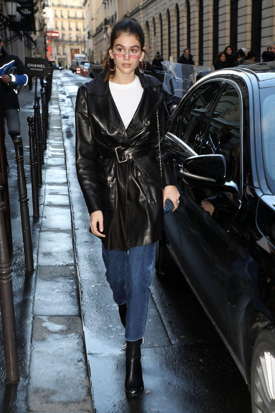 <p>Kaia arrives at Chanel office in Paris wearing a leather coat, bootcut means, black boots and a simple White t-shirt. She paired the look with half moon rose-tinted sunglasses. </p>