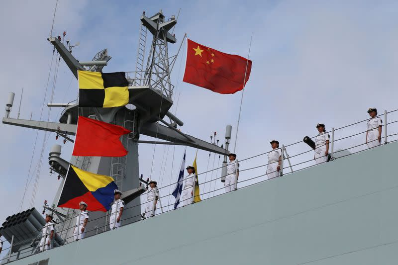 FILE PHOTO: Soldiers of China's People's Liberation Army (PLA) stand on a ship sailing off from a military port in Zhanjiang