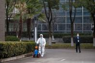 A worker in PPE disinfects the pavement after members of the World Health Organization (WHO) team arrived at the Hubei Animal Epidemic Disease Prevention and Control Center in Wuhan