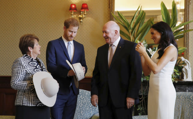Prince Harry and Meghan, Duchess of Sussex react as they receives traditional Australian hats from Australia's Governor General Sir Peter Cosgrove and his wife Lady Cosgrove.