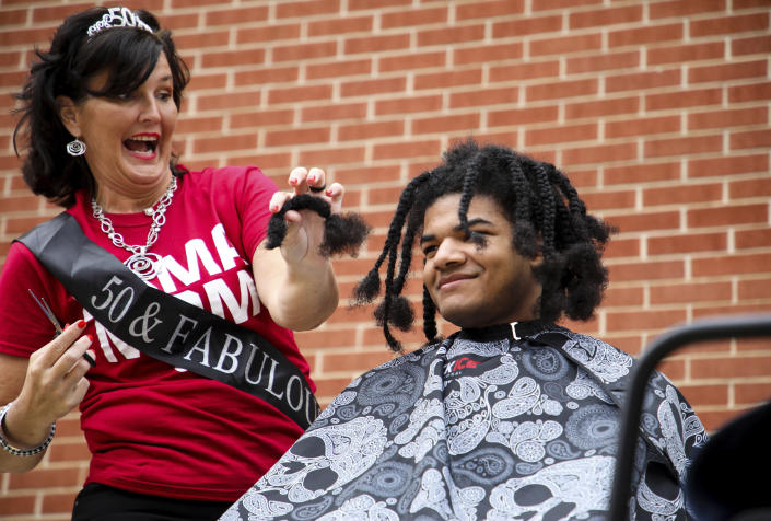 """In this photo provided by Gregg Gelmis, family friend Amber Bray, left, cuts a braid from Kieran Moïse's hair during a public fundraiser held to donate his 19-inch hair to the nonprofit Children with Hair Loss, Saturday, May 29, 2021, in Huntsville, Ala. Moïse also launched """"Kieran's Curls for Cancer"""" through St. Jude Children's Research Hospital in hopes of raising $1,000 per inch of hair. The goal was exceeded and has raised nearly $35,000. (Courtesy of Gregg Gelmis via AP)"""