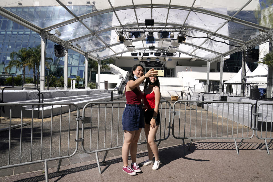Members of the public take a selfie photograph in front of the entrance to the Palais des Festival prior to the 74th international film festival, Cannes, southern France, July 5, 2021. The Cannes film festival runs from July 6 - July 17, 2021. (AP Photo/ Brynn Anderson)