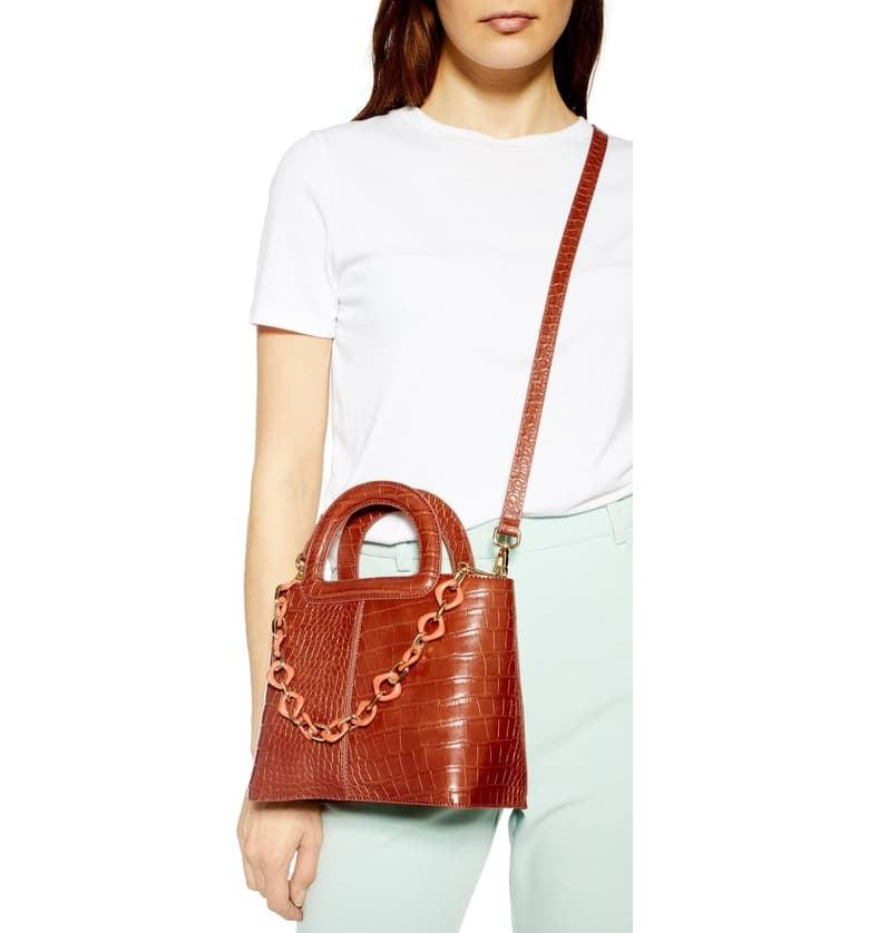"<p>The chain on this <a href=""https://www.popsugar.com/buy/Topshop-Tia-Croc-Embossed-Faux-Leather-Satchel-487268?p_name=Topshop%20Tia%20Croc%20Embossed%20Faux%20Leather%20Satchel&retailer=shop.nordstrom.com&pid=487268&price=45&evar1=fab%3Aus&evar9=46575569&evar98=https%3A%2F%2Fwww.popsugar.com%2Fphoto-gallery%2F46575569%2Fimage%2F46576076%2FTopshop-Tia-Croc-Embossed-Faux-Leather-Satchel&list1=shopping%2Cfall%20fashion%2Caccessories%2Cfall%2C50%20under%20%2450%2Caffordable%20shopping&prop13=api&pdata=1"" rel=""nofollow"" data-shoppable-link=""1"" target=""_blank"" class=""ga-track"" data-ga-category=""Related"" data-ga-label=""https://shop.nordstrom.com/s/topshop-tia-croc-embossed-faux-leather-satchel/5285015?origin=category-personalizedsort&amp;breadcrumb=Home%2FWomen%2FAccessories&amp;color=orange%20multi"" data-ga-action=""In-Line Links"">Topshop Tia Croc Embossed Faux Leather Satchel </a> ($45) is a cool touch.</p>"
