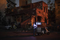 A man sells coffee in a neighborhood near the site of last week's massive explosion in Beirut, Lebanon, Friday, Aug. 14, 2020. (AP Photo/Felipe Dana)