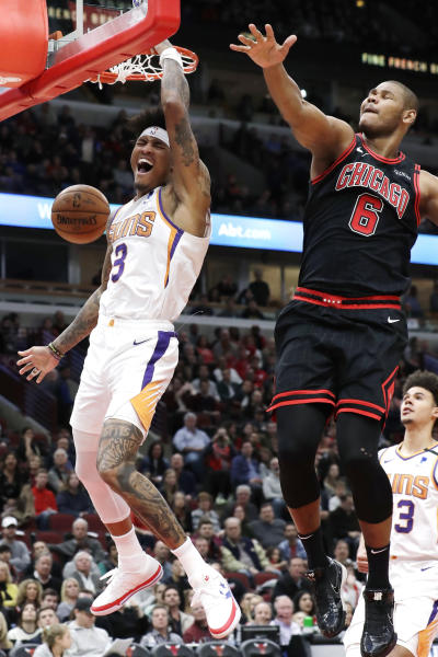 Phoenix Suns forward Kelly Oubre Jr., left, reacts as he dunks against Chicago Bulls forward/center Cristiano Felicio during the second half of an NBA basketball game in Chicago, Saturday, Feb. 22, 2020. (AP Photo/Nam Y. Huh)