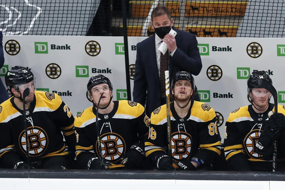 Boston Bruins head coach Bruce Cassidy stands behind his team as they look up at the scoreboard after a goal by Washington Capitals' Conor Sheary during the second period of an NHL hockey game, Sunday, April 11, 2021, in Boston. (AP Photo/Michael Dwyer)