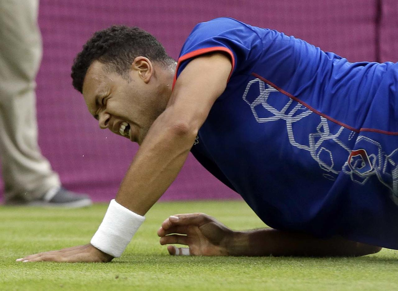 Jo-Wilfried Tsonga of France grimaces after falling on the grass during his match against Thomaz Bellucci of Brazil at the All England Lawn Tennis Club in Wimbledon, London at the 2012 Summer Olympics, Sunday, July 29, 2012. (AP Photo/Elise Amendola)