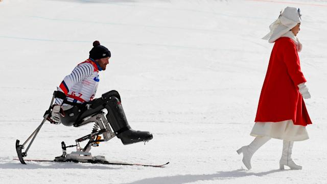 Alpine Skiing - Pyeongchang 2018 Winter Paralympics - Men's Slalom - Sitting - Final - Jeongseon Alpine Centre - Jeongseon, South Korea - March 17, 2018 - Frederic Francois of France follows a medal host girl to the victory ceremony after winning the bronze. REUTERS/Paul Hanna TPX IMAGES OF THE DAY