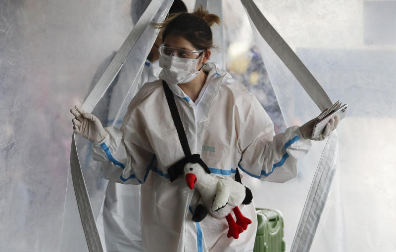 A woman in protective suit passes by a disinfection tent before she enters the departure area of Manila's International Airport, Philippines on Friday, May 22, 2020. Some airlines began flights in and out of the country as the capital eases it's lockdown while it continues to fight the spread of the new coronavirus. (AP Photo/Aaron Favila)