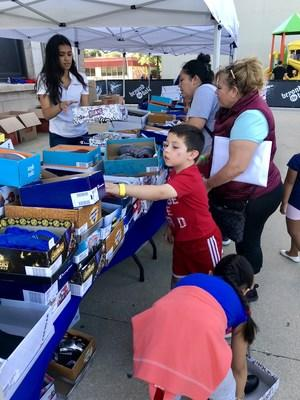Children picking out shoes at the Hilco Global back-to-school shoe giveaway.