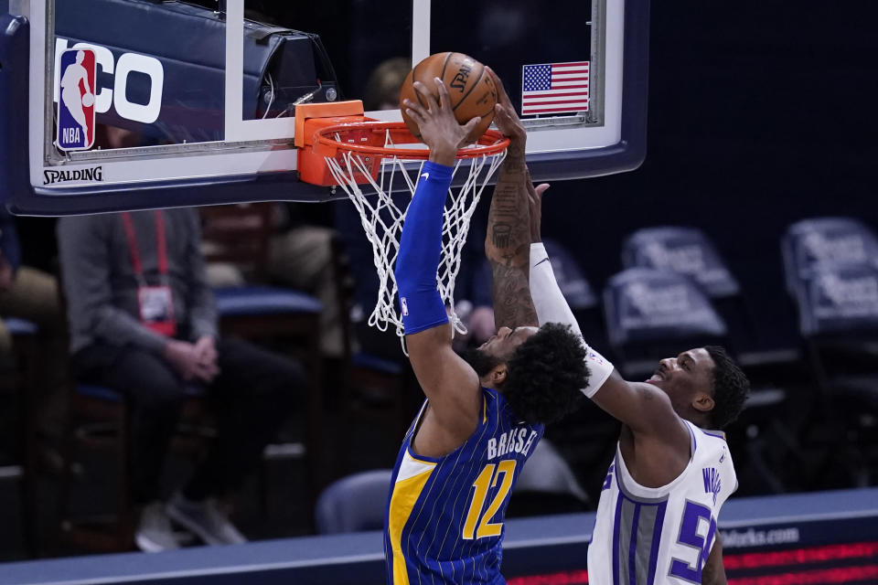 Indiana Pacers' Oshae Brissett (12) dunks against Sacramento Kings' Delon Wright (55) during the first half of an NBA basketball game Wednesday, May 5, 2021, in Indianapolis. (AP Photo/Darron Cummings)