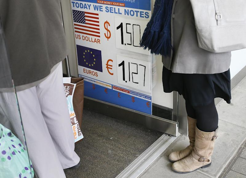 People queue at a money exchange bureau, in London, Monday, Feb. 25, 2013. The British pound fell sharply against other currencies before stabilizing somewhat on Monday as investors reacted to the downgrade of the U.K.'s cherished triple-A credit rating. (AP Photo/Kirsty Wigglesworth)