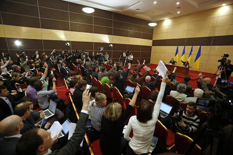 Ukraine's fugitive President Viktor Yanukovych, back left, gives a news conference as journalists raise arms to ask questions, in Rostov-on-Don, a city in southern Russia about 1,000 kilometers (600 miles) from Moscow, Friday, Feb. 28, 2014. Yanukovych has pledged to fight on for the country's future. (AP Photo/Pavel Golovkin)