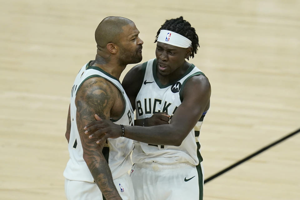 Milwaukee Bucks forward P.J. Tucker, left, celebrates with guard Jrue Holiday during the second half of Game 5 of basketball's NBA Finals against the Phoenix Suns, Saturday, July 17, 2021, in Phoenix. (AP Photo/Ross D. Franklin)