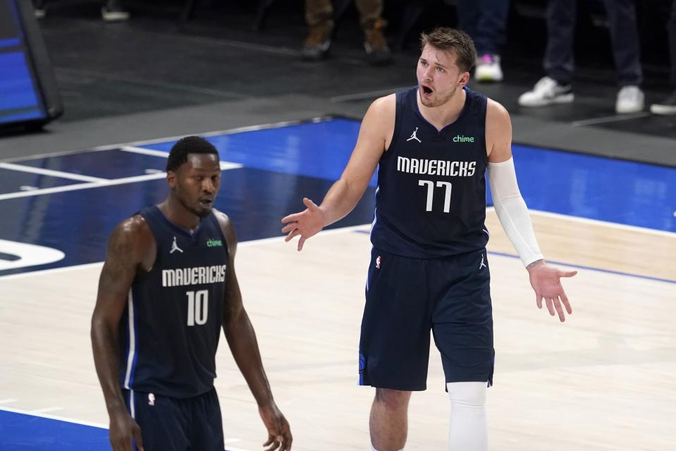 Dallas Mavericks guard Luka Doncic (77) reacts to play as forward Dorian Finney-Smith (10) walks past in the first half in Game 3 of an NBA basketball first-round playoff series against the Los Angeles Clippers in Dallas, Friday, May 28, 2021. (AP Photo/Tony Gutierrez)