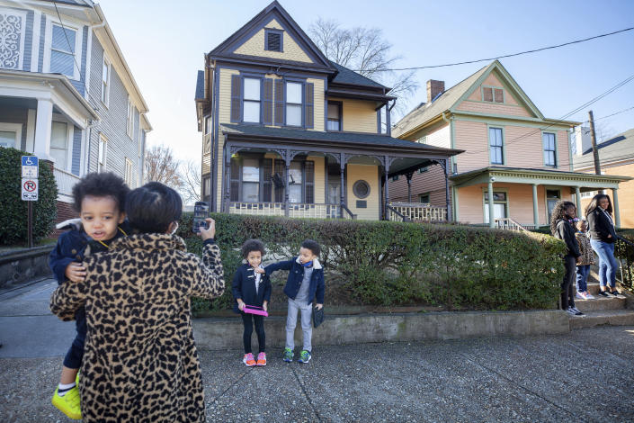 Alexis Upshaw, left, holding 2-year-old Ari Upshaw, takes a photo as Ty Upshaw, 7, right, adjusts the mask of his sister, Mila Upshaw, 5, in front of the birthplace of Dr. Martin Luther King, Jr. on Monday, Jan. 18, 2021, the Martin Luther King Jr. holiday, in Atlanta. (AP Photo/Branden Camp)