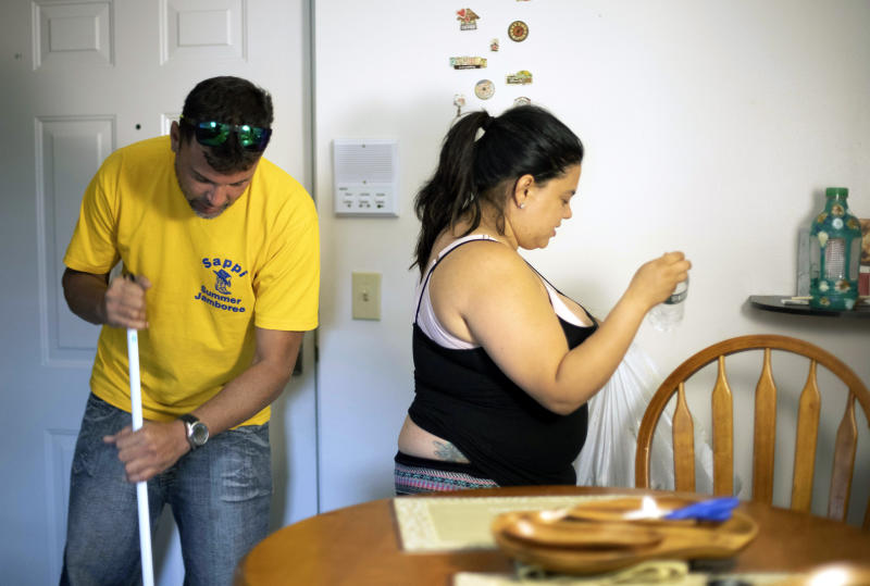 In this Aug. 2, 2019 photo, Ashlyn Gonzales, right, and her longtime partner Emanuel Rivera clean their condo after work in Portland, Conn. In the months after Hurricane Maria destroyed her home in Puerto Rico, Gonzales moved to Connecticut, where federal and state aid helped her and Rivera avoid homelessness. But aid at both levels has just about dried up, leaving Gonzales and many like her wondering what they are going to do next. (AP Photo/Chris Ehrmann)