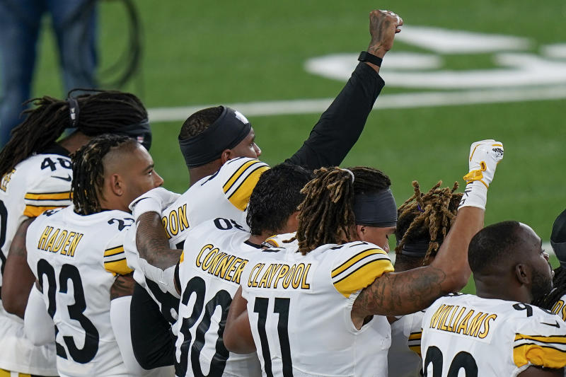 Pittsburgh Steelers players react during the national anthem