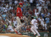 Los Angeles Angels starting pitcher Dillon Peters walks on the mound as Boston Red Sox's Sam Travis rounds the bases after hitting a two-run home run during the second inning of a baseball game at Fenway Park, Thursday, Aug. 8, 2019, in Boston. (AP Photo/Elise Amendola)