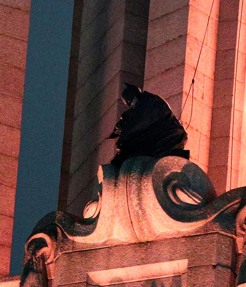 A man dressed as Batman on the top of one of the Three Graces during the filming of The Batman in Liverpool. (PA)
