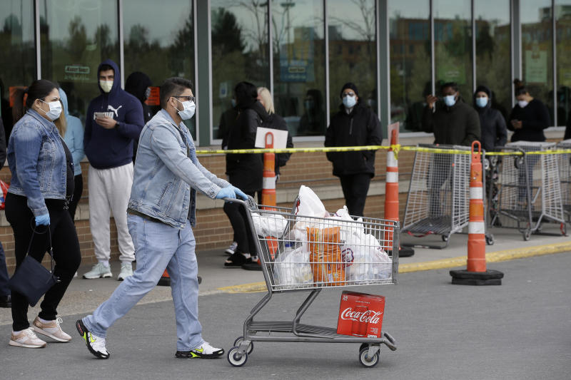 A man pushes a grocery cart, front, while wearing a mask out of concern for the coronavirus as he walks past a line of safely distanced shoppers waiting to enter a supermarket, Sunday, April 26, 2020, in Chelsea, Mass. (AP Photo/Steven Senne)