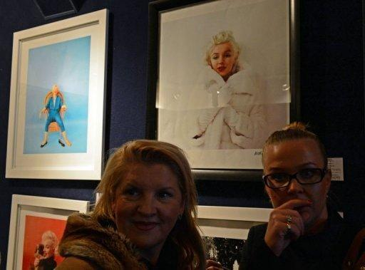 Two women stand in front of pictures showing Marilyn Monroe during an auction of photographs by late celebrity photographer Milton Greene, in Warsaw, Poland. Fans snapped up over 230 photos of the tragic star and other big Hollywood names for $740,000