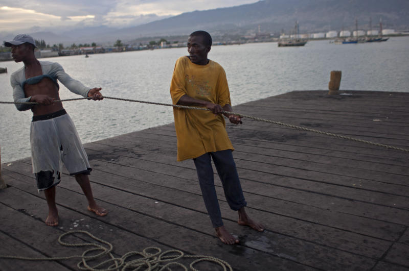 Fishermen pull on a rope in Port Cite Soleil in Port-au-Prince, Haiti, Friday, Aug. 24, 2012. Tropical Storm Isaac strengthened slightly as it spun toward the Dominican Republic and Haiti, but seemed unlikely to gain enough steam early Friday to strike as a hurricane. The storm's failure to gain the kind of strength in the Caribbean that forecasters initially projected made it more likely that Isaac won't become a hurricane until it enters the Gulf of Mexico, said Eric Blake, a forecaster with U.S. National Hurricane Center in Miami. (AP Photo/Dieu Nalio Chery)