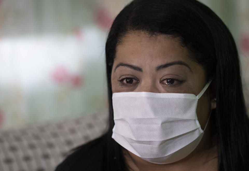 "Nurse Lidiane Melo cries during an interview with The Associated Press at her home in Rio de Janeiro, Brazil, Wednesday, April 14, 2021. In the early days of the pandemic, as sufferers were calling out for comfort that she was too busy to provide, Melo filled two rubber gloves with warm water, knotted them shut, and sandwiched them around a patient's hand, to re-create a loving clasp. Some have christened the practice the ""hand of God,"" and it is now the searing image of a nation roiled by a medical emergency with no end in sight. (AP Photo/Silvia Izquierdo)"