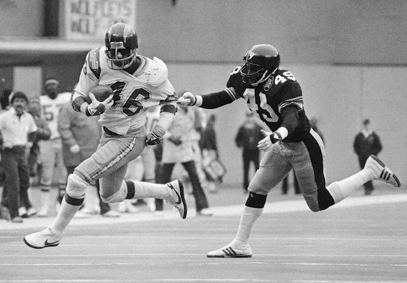 FILE - In this Jan. 19, 1983, file photo, San Diego Chargers Chuck Muncie breaks free from Pittsburgh Steelers defender Dwayne Woodruff as he runs for a gain during the fourth quarter of an NFL football playoff game in Pittsburgh. The New Orleans Saints announced Tuesday, May 14, 2013, that Muncie, a Pro Bowl running back with both the Saints and Chargers, has died. He was 60. (AP Photo/Rusty Kennedy, File)