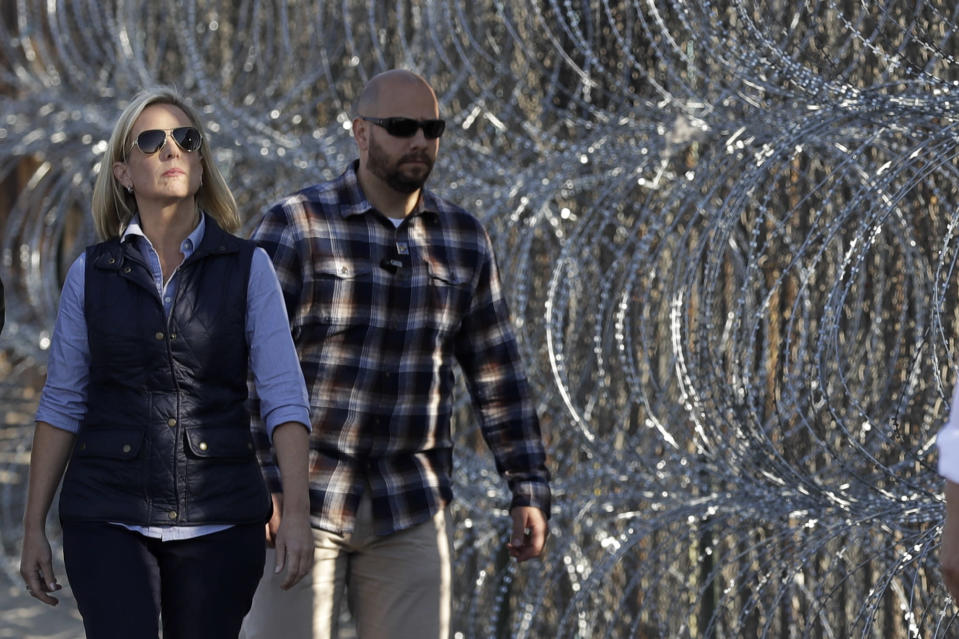 Secretary of Homeland Security Kirstjen Nielsen, left, walks next to a section of the border wall fortified with razor wire separating San Diego from Tijuana, Mexico, on Nov. 20, 2018. (Photo: Gregory Bull/AP)