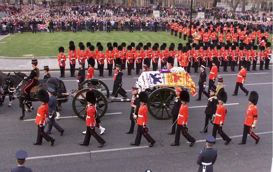 Guardsmen present arms as the coffin of Queen Elizabeth the Queen Mother passes through London's Parliament Square during funeral ceremonies on April 9, 2002.