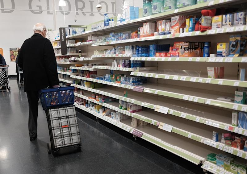 A man with a shopping trolley walking past empty shelves in a Sainsbury's store in London, as the death toll from coronavirus in the UK reached 71 people.