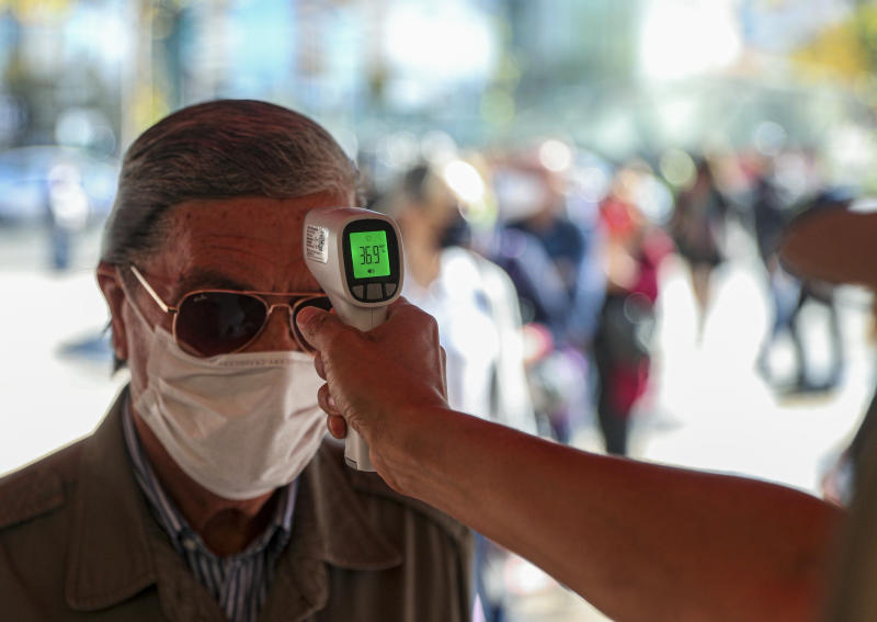A city worker measures the temperature of a man before entering the Apumanque shopping center in Las Condes neighborhood, in Santiago, Chile, Thursday, April, 30, 2020. As Chilean authorities look to ease COVID-19 related quarantine measures, the well-known shopping mall in the upscale neighborhood opened to the public for the first time on Thursday since lockdown began over one month ago. (AP Photo/Esteban Felix)