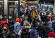 People wear face masks but stand close together as they wait for a subway train in Frankfurt, Germany, Wednesday, Dec. 2, 2020. (AP Photo/Michael Probst)