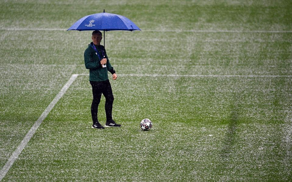 A match official inspects the pitch as hailstones fall prior -  Laurence Griffiths/Getty Images