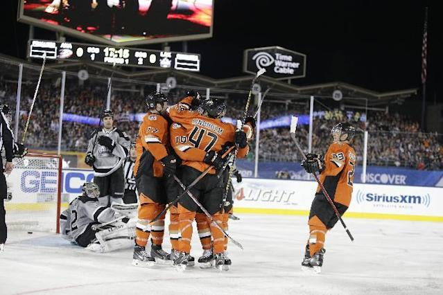 The Anaheim Ducks celebrate a goal by right wing Corey Perry as Los Angeles Kings goalie Jonathan Quick, lower left, sits on the ice during the first period of an NHL outdoor hockey game at Dodger Stadium in Los Angeles, Saturday, Jan. 25, 2014. (AP Photo/Chris Carlson)
