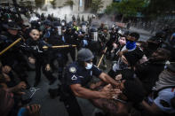 Police officers and protesters clash near CNN Center, May 29, 2020, in Atlanta, in response to George Floyd's death. The protest started peacefully earlier in the day before demonstrators clashed with police. The image was part of a series of photographs by The Associated Press that won the 2021 Pulitzer Prize for breaking news photography. (AP Photo/Mike Stewart)