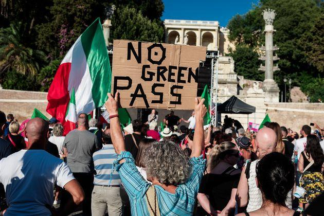 ROME, ITALY - AUGUST 07: A demonstrator holds up a banner during a demonstration in Piazza del Popolo, organized by the No Vax and far-right movements against the