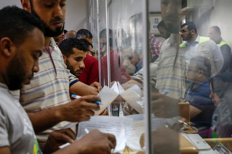 Palestinians wait inside a Gaza City post office to receive Qatari cash aid (AFP Photo/MOHAMMED ABED)