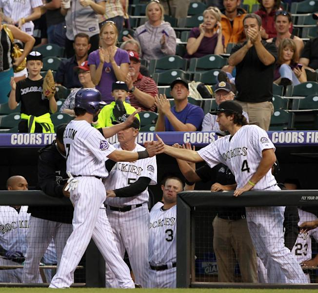 Colorado Rockies' Todd Helton, left, is congratulated by Ryan Wheeler as Helton returns to the dugout after driving in two runs with a single against the Arizona Diamondbacks in the ninth inning of a baseball game in Denver on Sunday, Sept. 22, 2013. The Diamondbacks won 13-9. Helton, who announced that he will retire at season's end after 17 years with the Rockies, drove in four runs in the game. (AP Photo/David Zalubowski)