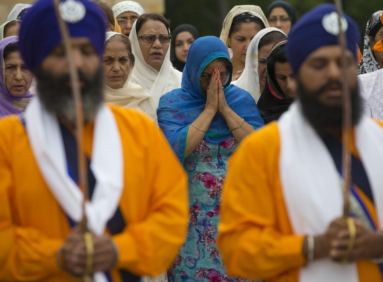 People attend a prayer service being held outside the Sikh Temple of Wisconsin in Oak Creek, Wis., Sunday, Aug. 12, 2012. More than 100 people gathered for the first Sunday prayer service since a white supremacist shot and killed six people there before fatally shooting himself. (AP Photo/Jeffrey Phelps)