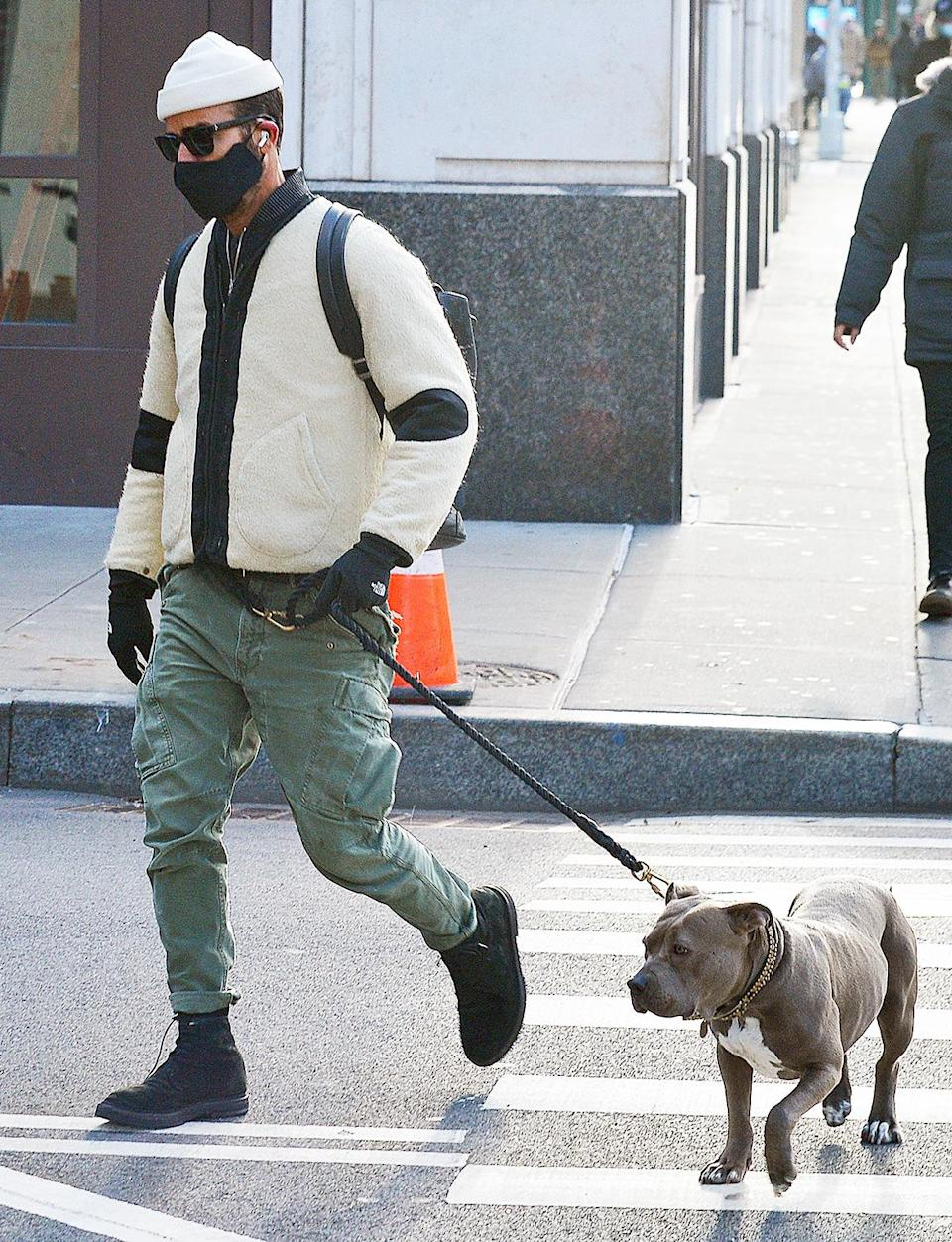 <p>A masked Justin Theroux takes his dog Kuma out in N.Y.C. on Wednesday.</p>
