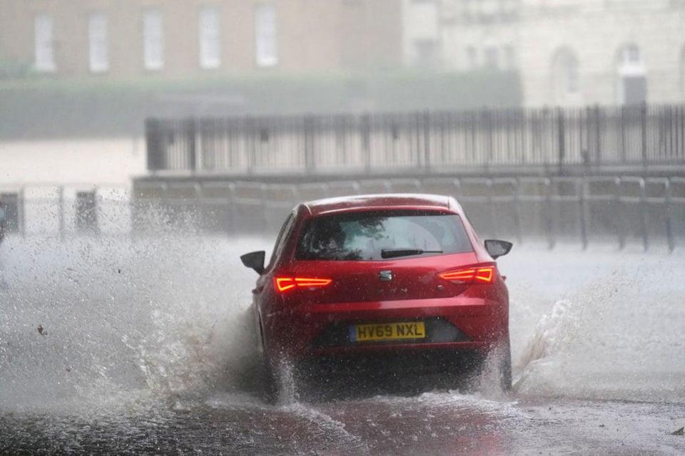 A car drives through flood water in Horse Guards Road in central London in July, as similar scenes are predicted amid a yellow warning for rain covering the capital until midnight on Tuesday (Victoria Jones/PA). (PA Wire)