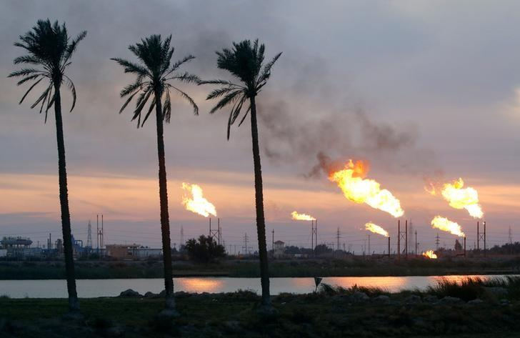 FILE PHOTO: Flames emerge from flare stacks at the oil fields in Basra
