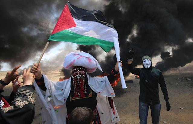 <p>A Palestinian man holding a flag walks in the smoke billowing from burning tires next to a protester wearing an Anonymous mask during clashes with Israeli forces along the border with the Gaza Strip east of Khan Younis on May 14, 2018, as Palestinians protest the inauguration of the U.S. Embassy following its controversial move to Jerusalem. (Photo: Said Khatib/AFP/Getty Images) </p>