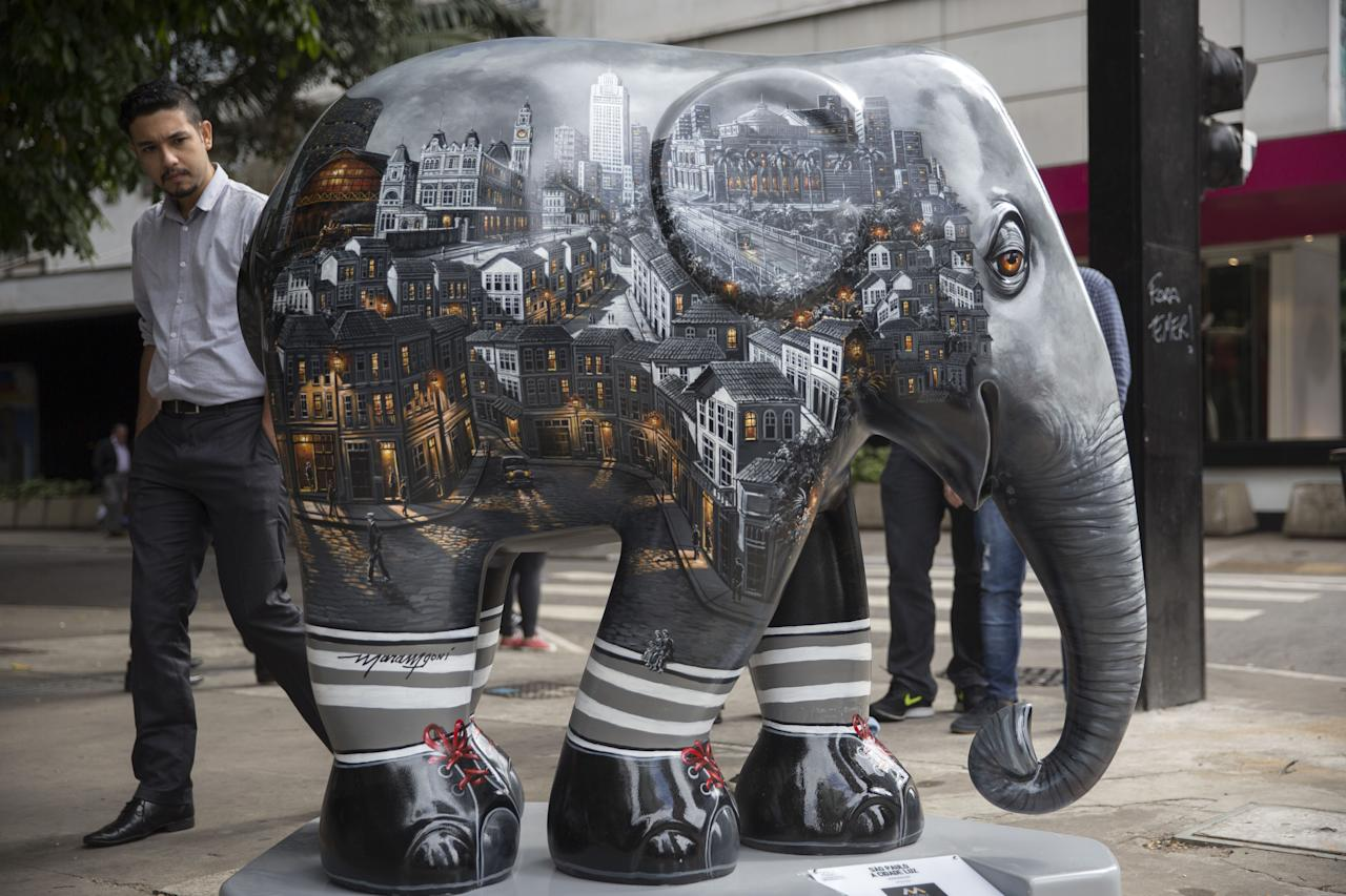 <p>A passer-by looks on an elephant sculpture as part of the 'Elephant Parade' at the Paulista Avenue in Sao Paulo, Brazil, 01 August 2017. Aug. 1, 2017. (Photo: Sebastiao Moreira/EPA/REX/Shutterstock) </p>