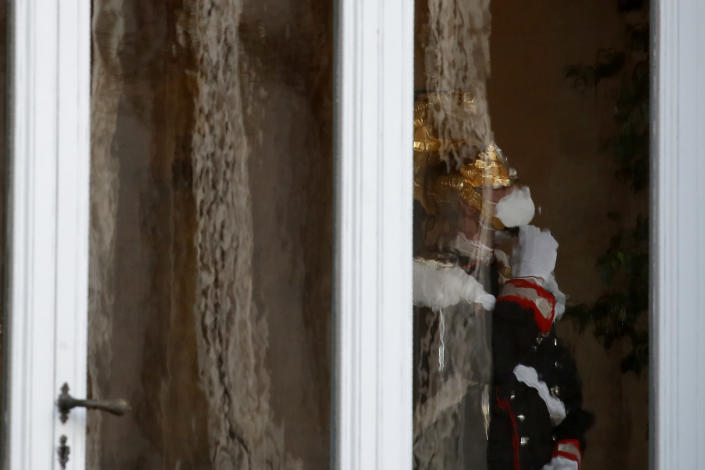 A Cuirassier Regiment presidential guard stands behind a window of the Quirinale presidential palace, in Rome, Wednesday, Jan. 27, 2021. Italian Premier Giuseppe Conte resigned after a key coalition ally pulled his party's support over Conte's handling of the coronavirus pandemic, setting the stage for consultations this week to determine if he can form a third government.(AP Photo/Alessandra Tarantino)